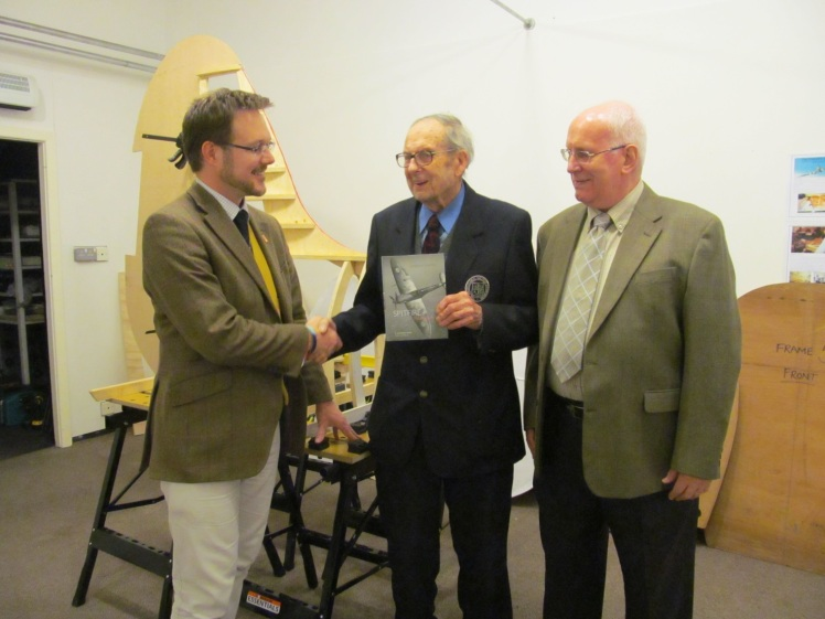George Mobbs, (centre) presenting Dominic Berry (left) with the Spitfire book in front of The Ratcliffe Spitfire project.
